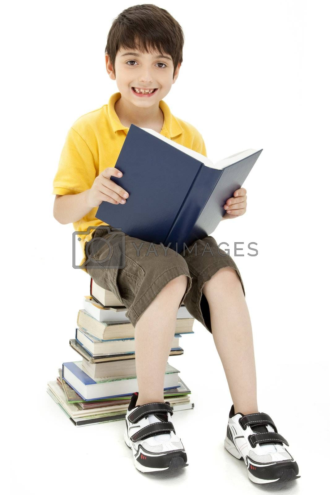 Attractive boy child sitting on large stack of books reading.