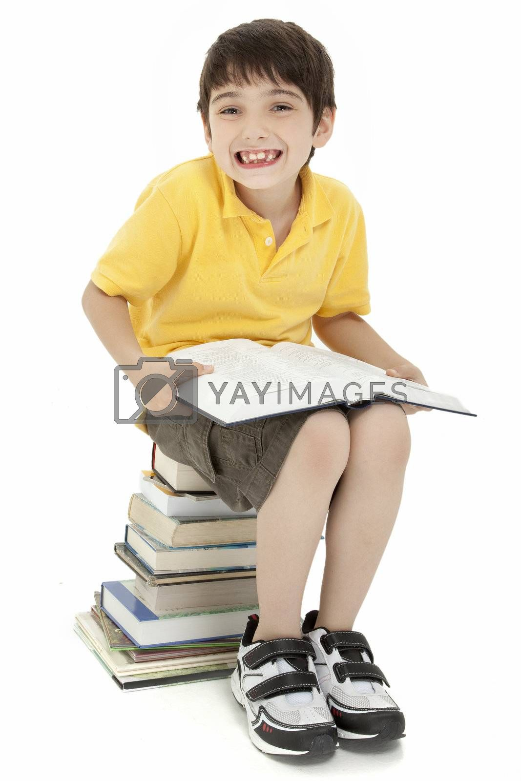 Excited elementary age school boy child sitting on stack of books reading.