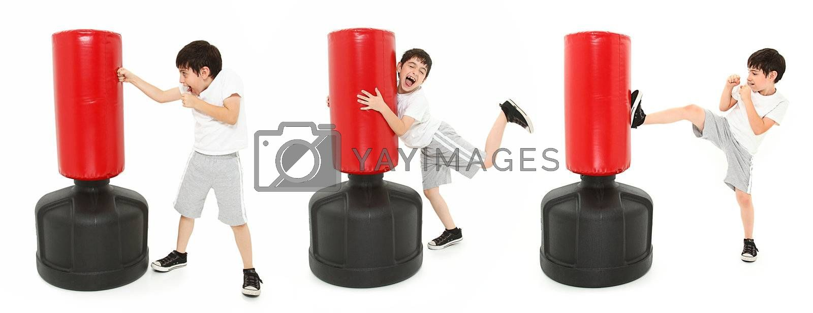 Adorable 8 year old boy practicing kicks and punches with a free standing heavy bag over white.