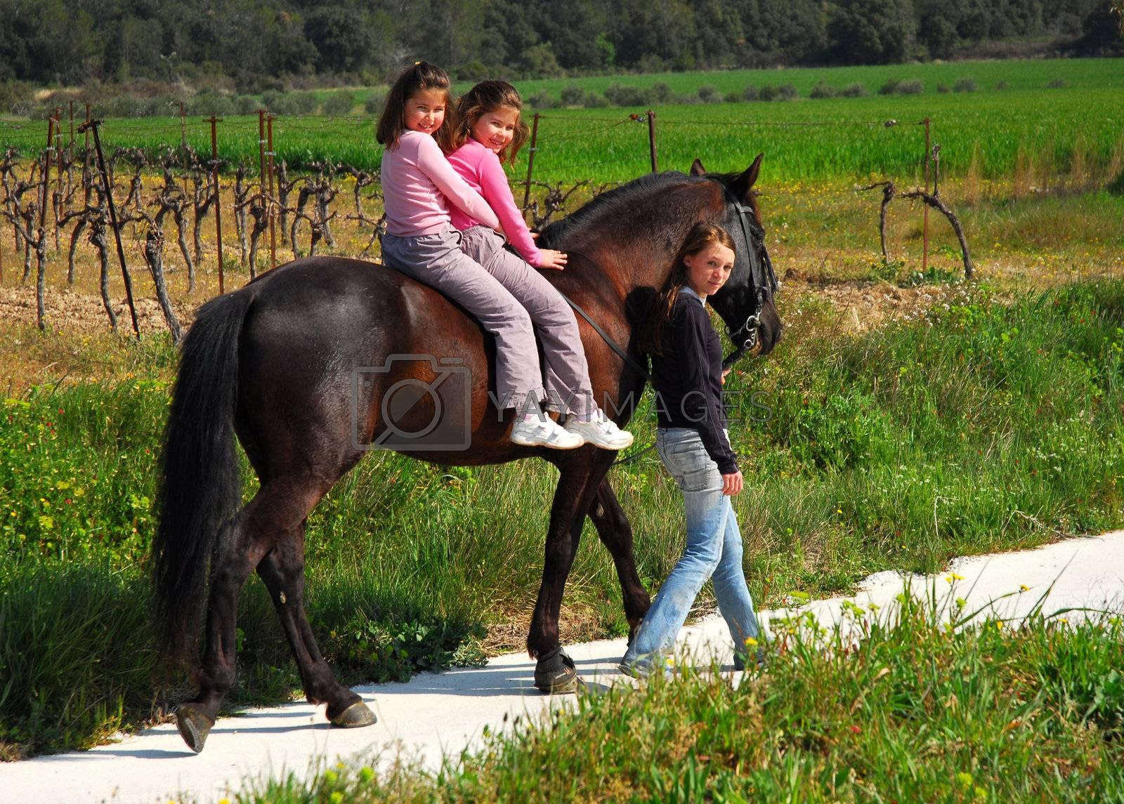 twins sisters horseback riding a black stallion