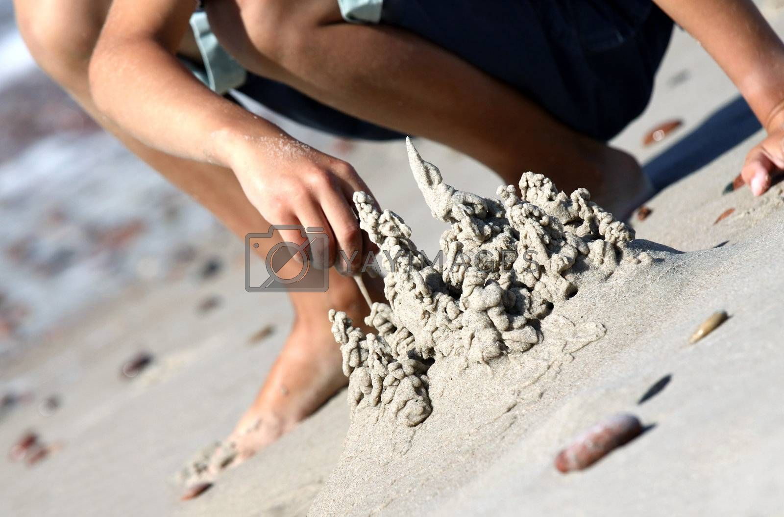 Picture of a boy hand building sand castle on the beach