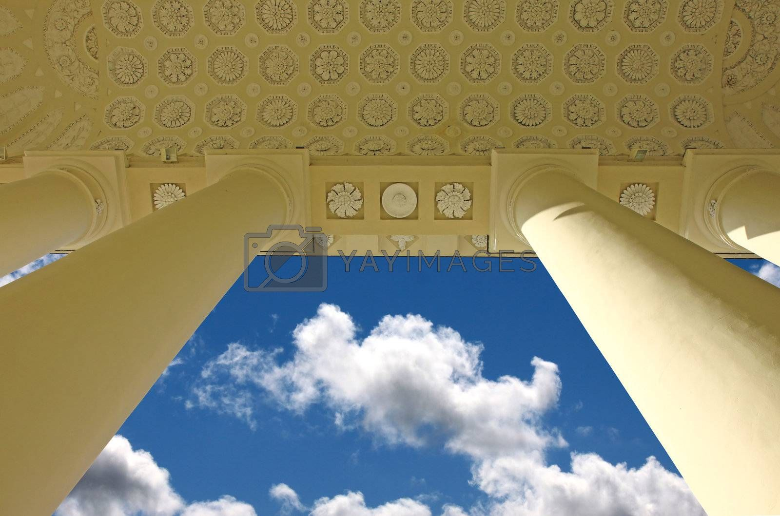 Outdoor ceiling of the classic style building with columns and blue sky