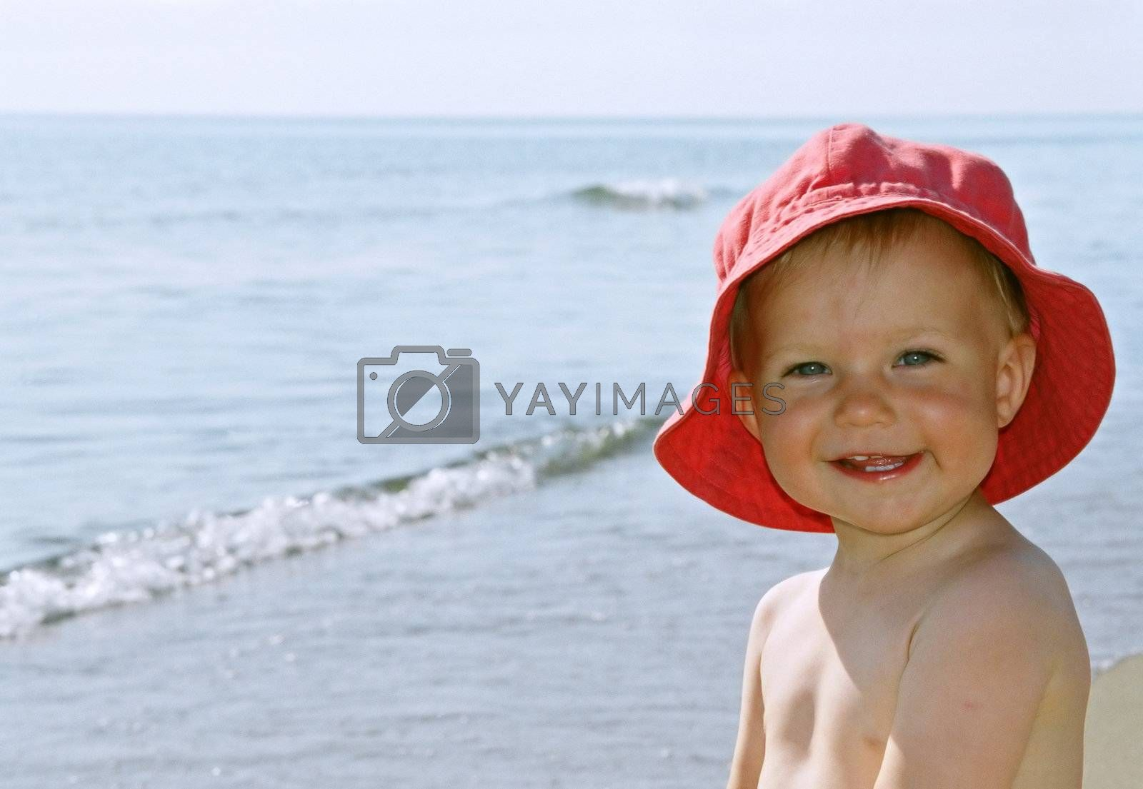 Happy smiling little girl with red hat by the sea