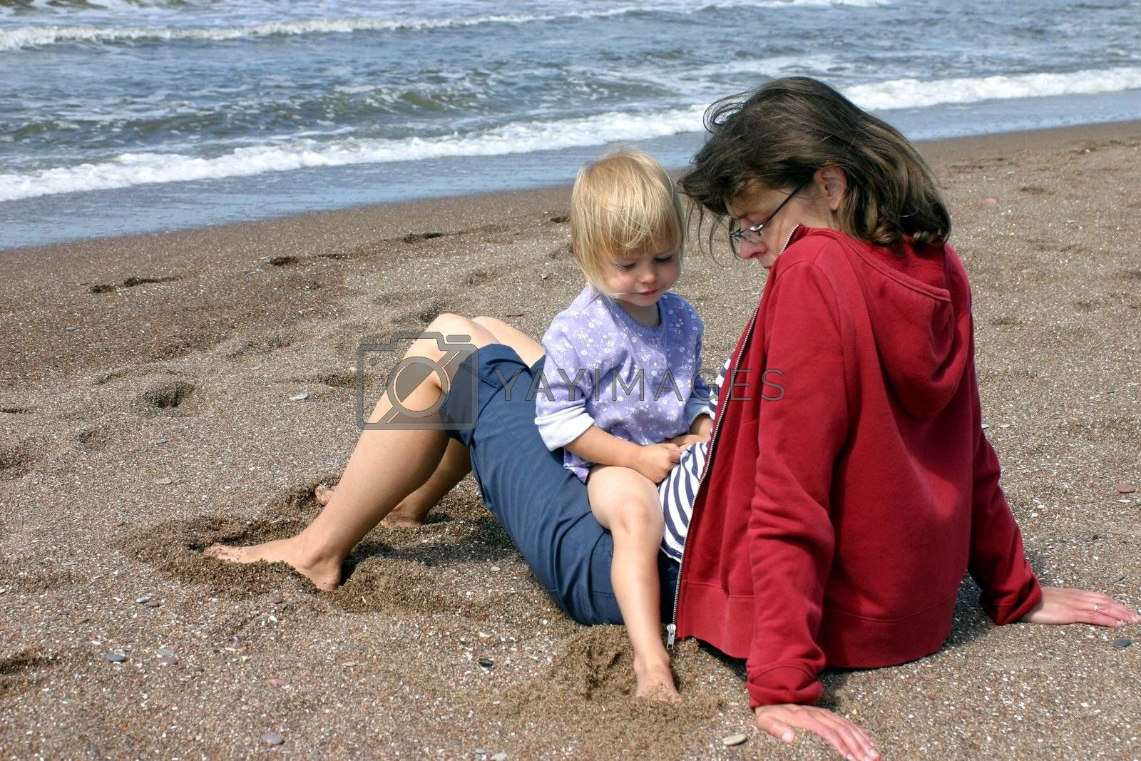 Mother and her little daughter sitting on the beach