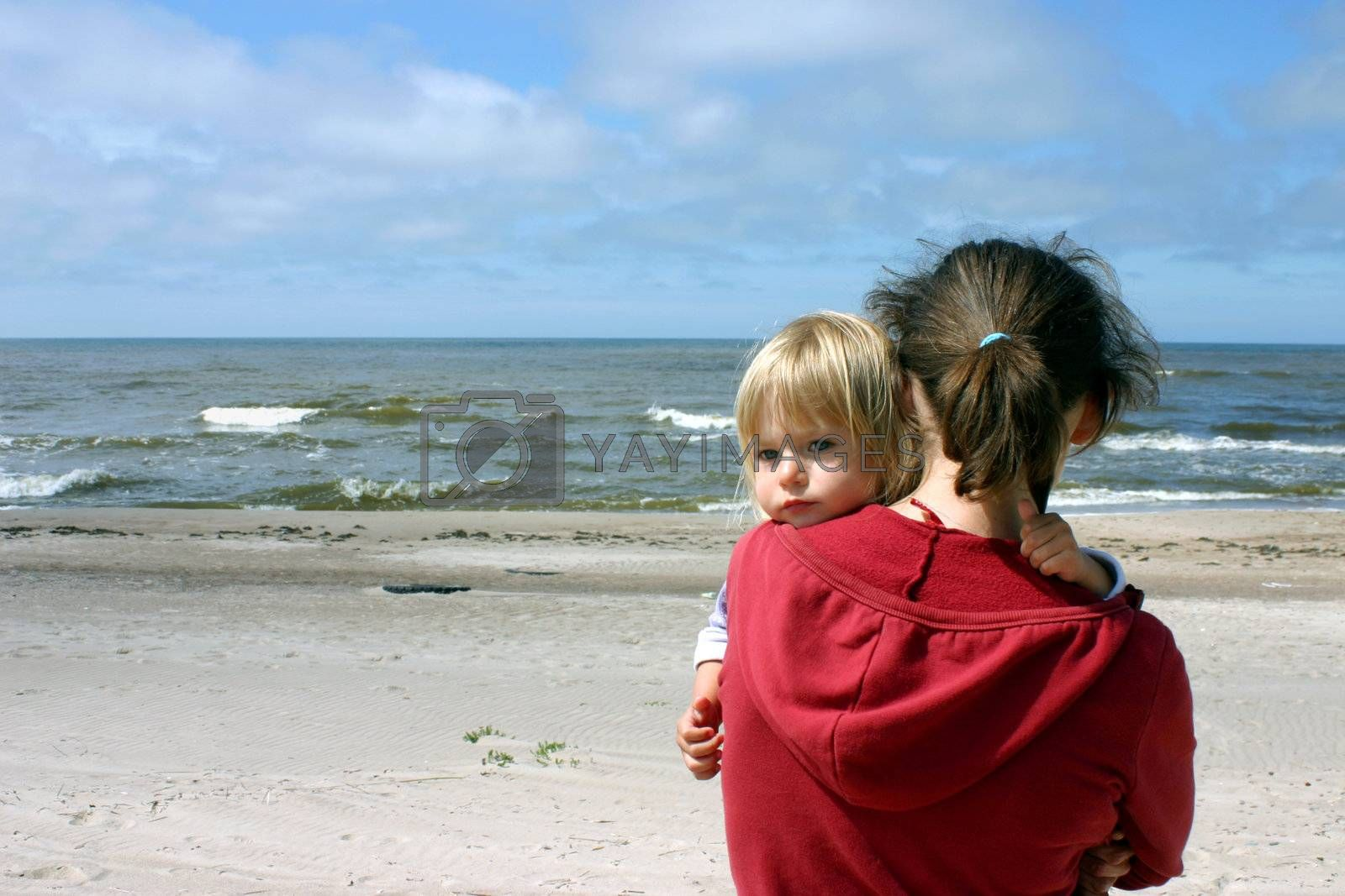 Mother with little daughter on her hands standing by the sea