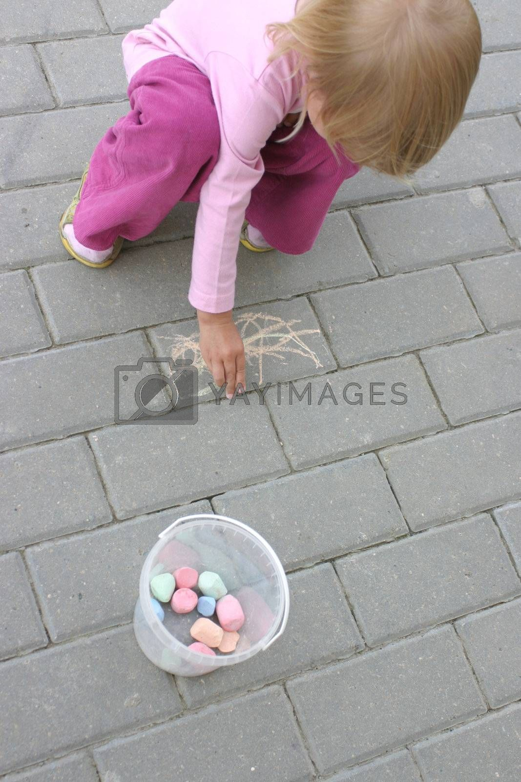 Little girl painting with crayon on the pavement