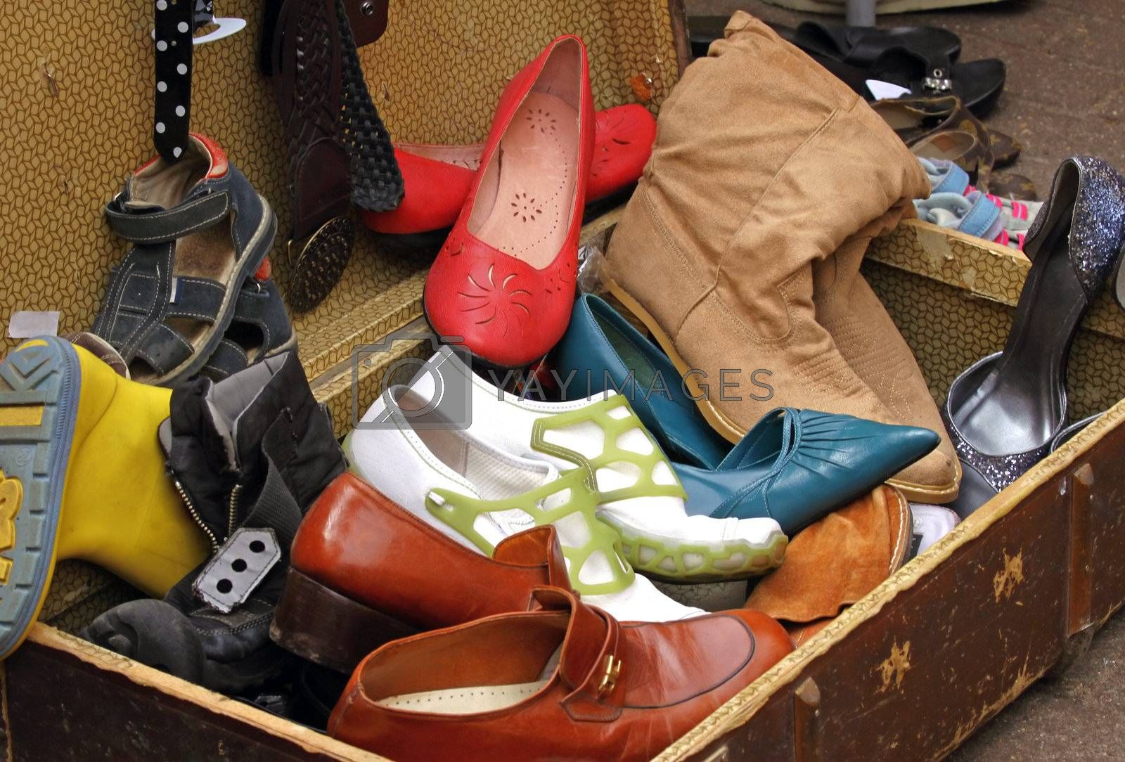 Suitcase full of old worn out shoes at flea market