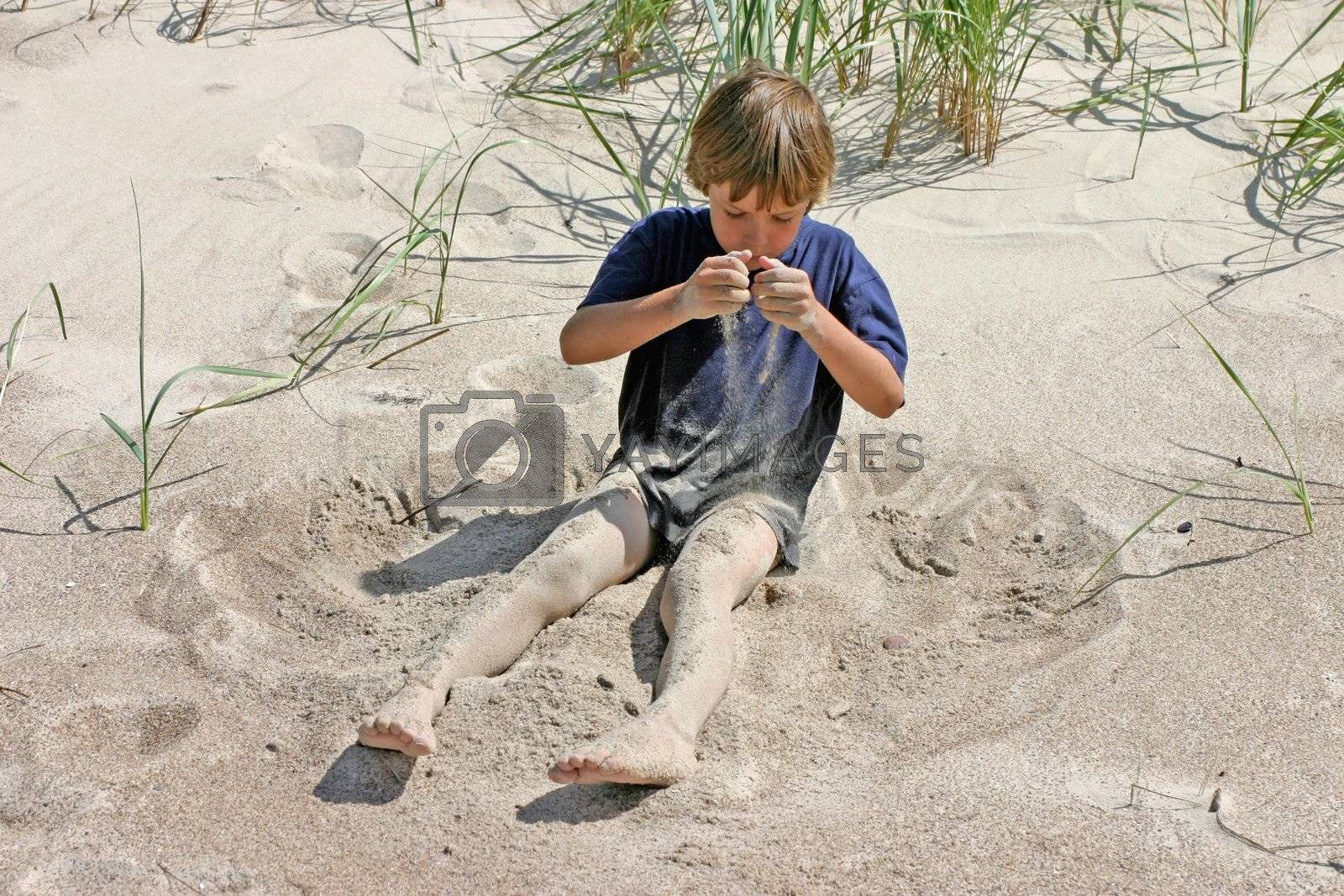 7-9 years old boy playing with sand on the beach