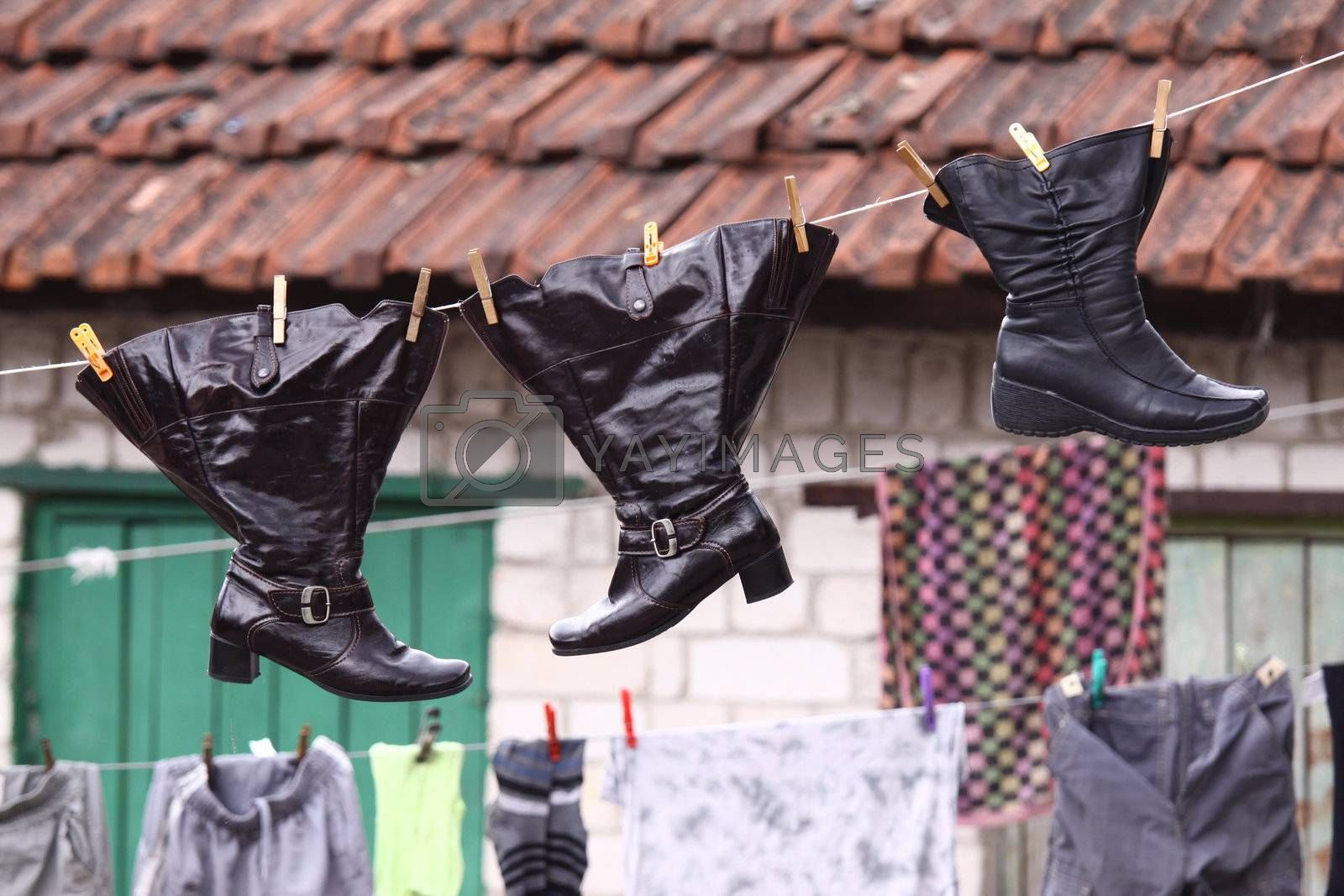 Wet shoes hanging on the clothesline along with other laundry