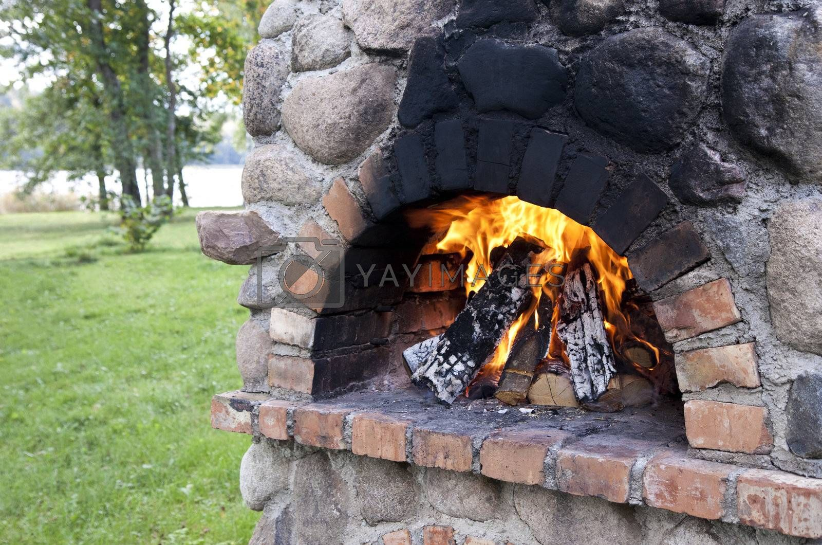 Stationary barbecue fireplace with burning wood at summer day