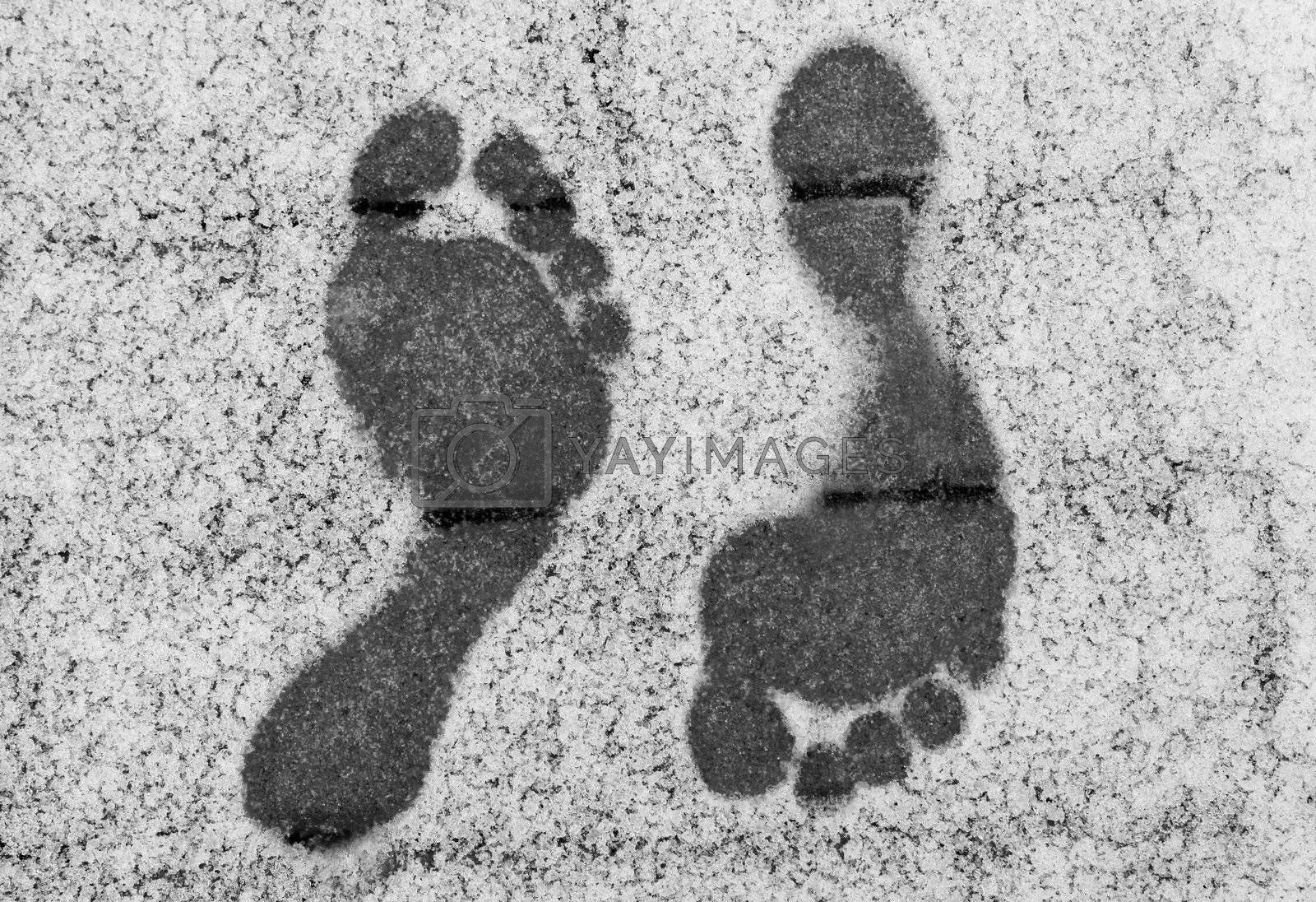 Two opposite barefoot footprints on snow at winter