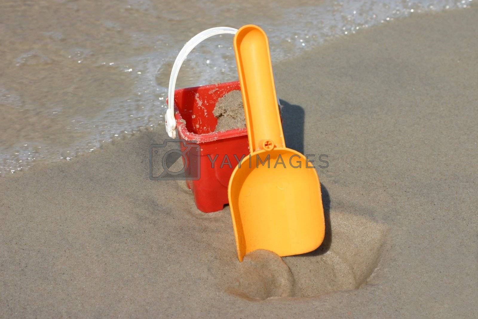 Toy bucket and shovel on the beach, plenty of copy space