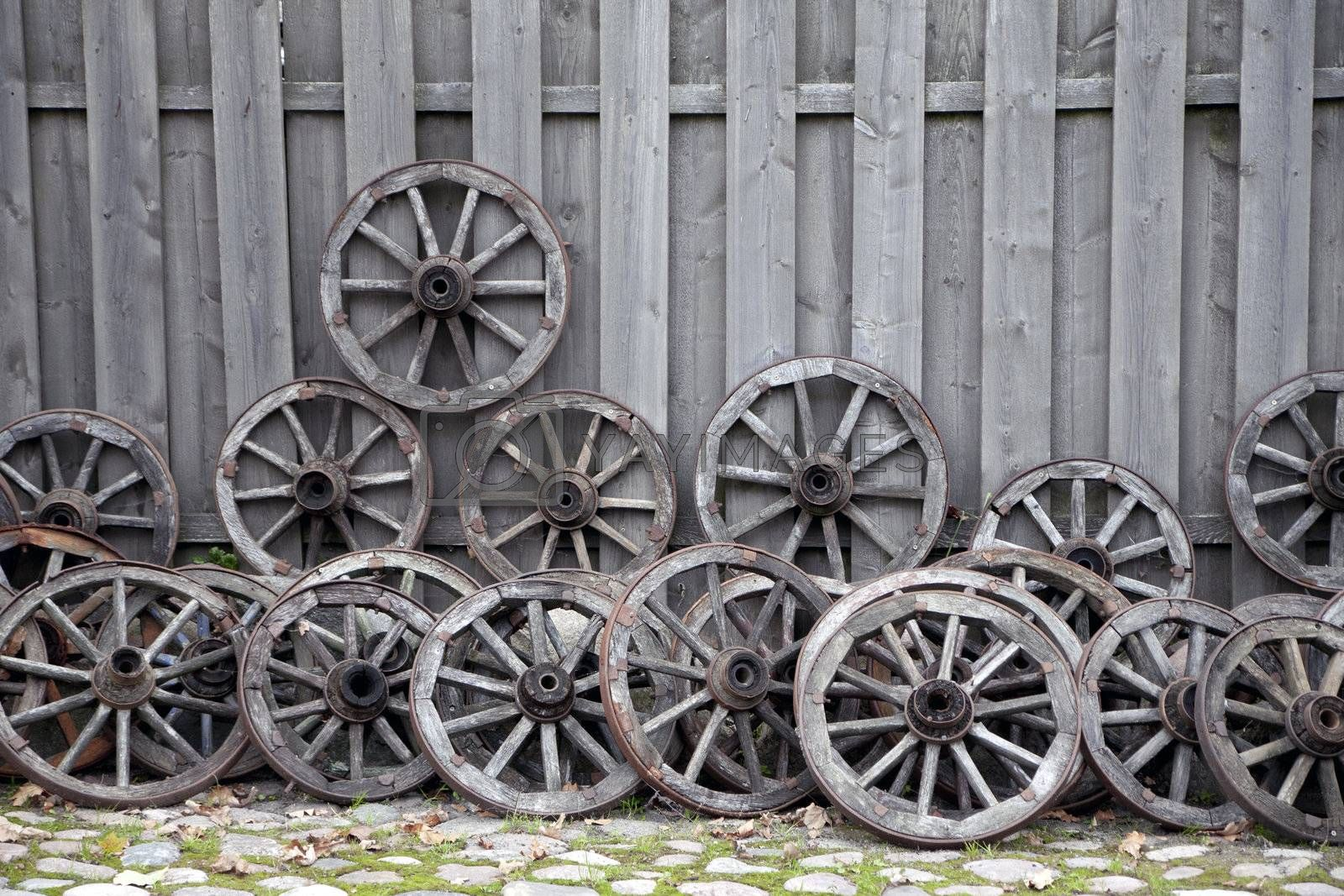 Bunch of old wooden carriage wheels against wooden fence