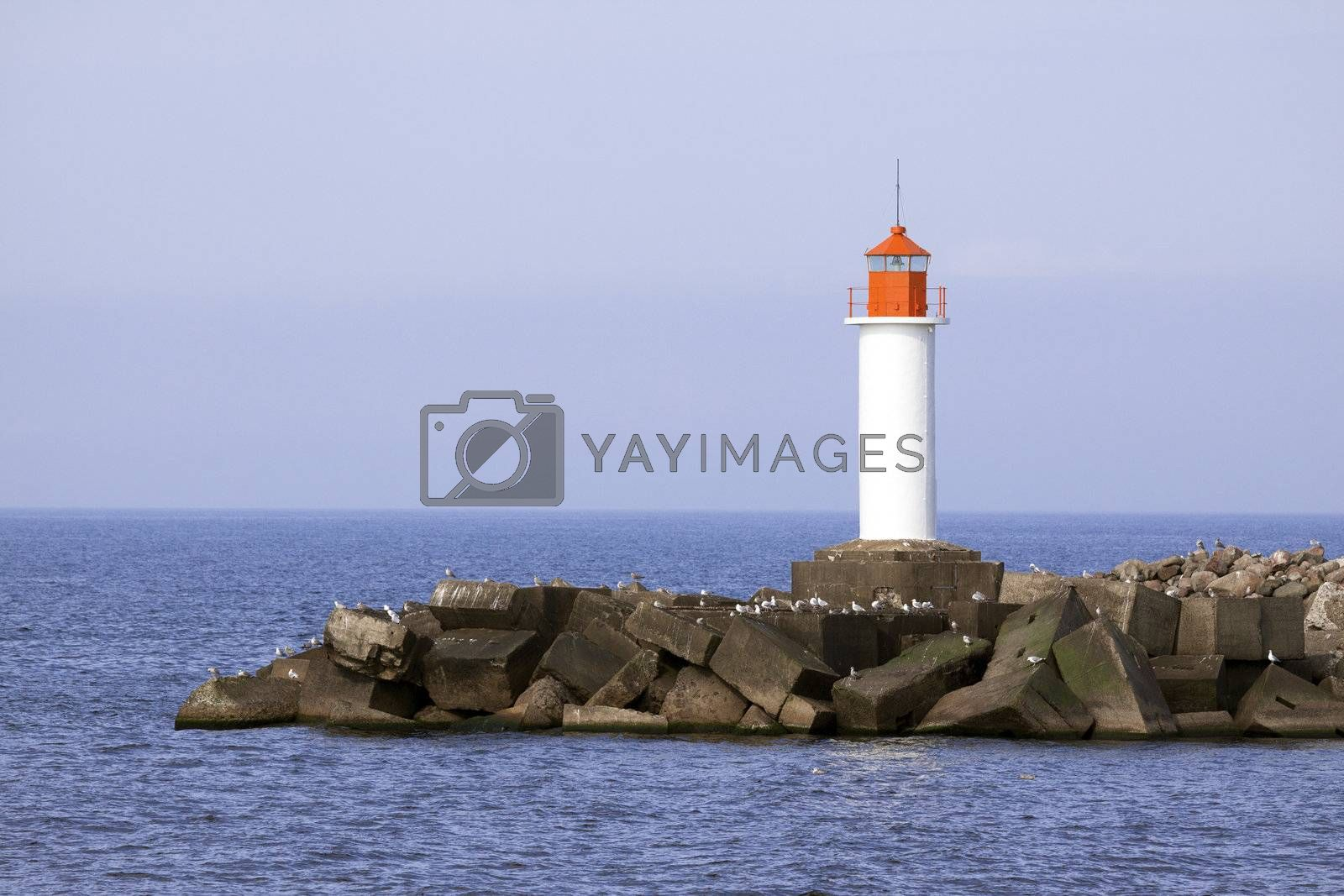 White lighthouse and stone pier in Ventspils, Latvia