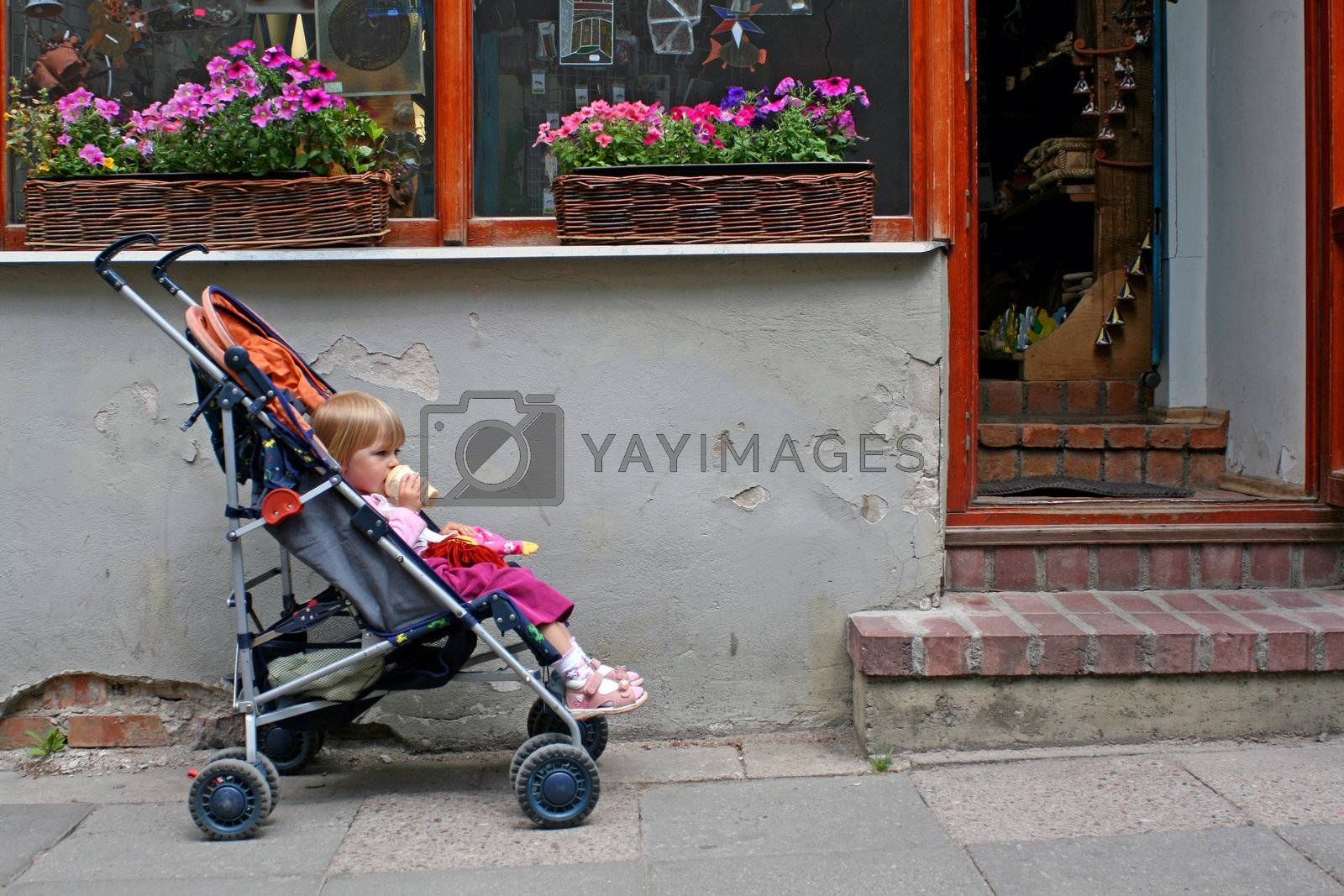 2-3 years old child sitting in the pram in front of the shop doors, eating ice cream and waiting for parent