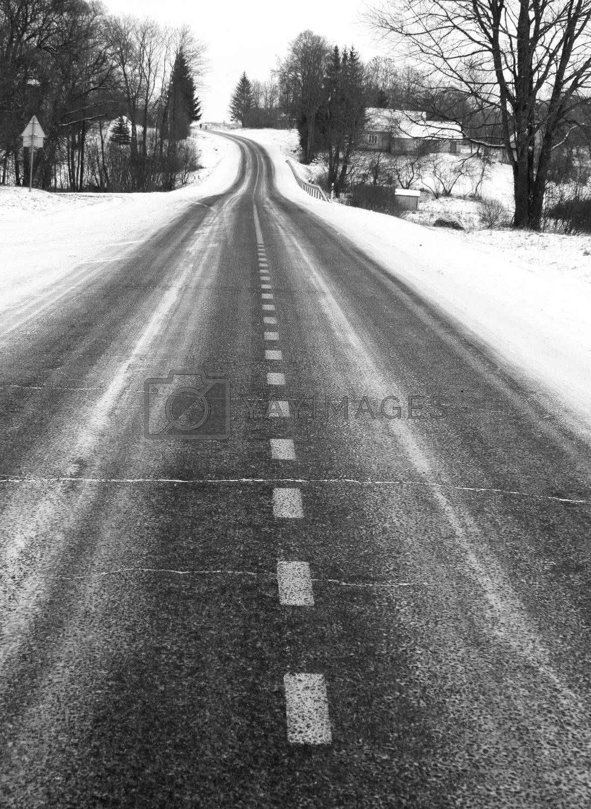 Black and white picture of the country road in winter, focus on dividing line