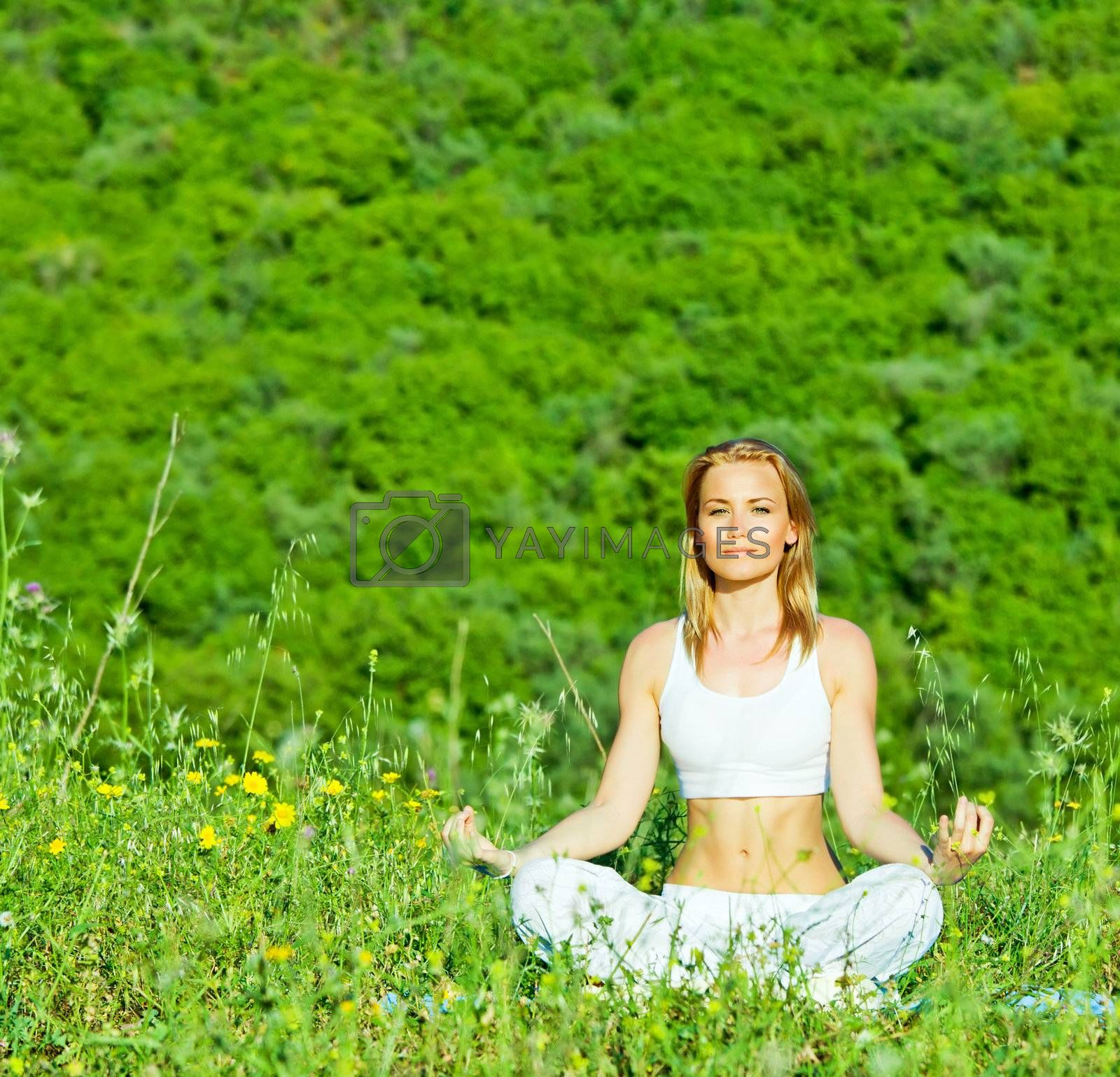 Photo of beautiful woman doing yoga exercise outdoors, mental health, healthy lifestyle, cute young lady sitting in lotus pose, pretty girl is engaged in fitness in park over green tree background