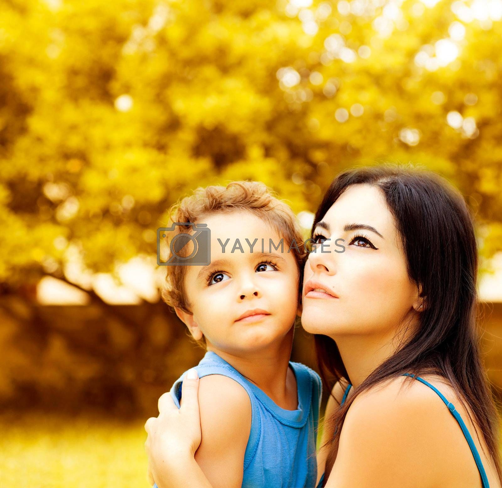 Photo of beautiful woman with little son on backyard in autumn, portrait of mother hugging adorable baby boy, young family playing games in autumn park, happy childhood, love concept