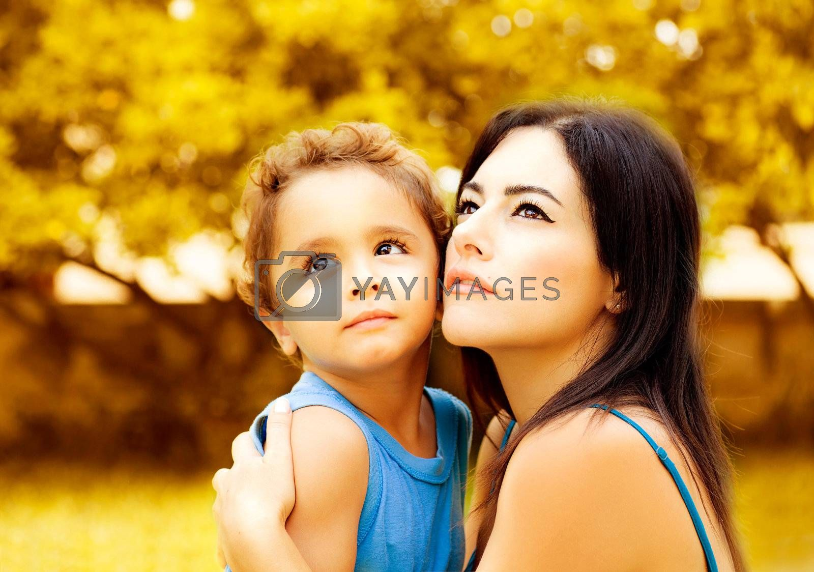 Picture of pretty female with son looking up, young mother hugging cute child, adorable boy with mommy having fun outdoors in autumn, fall season, happy family and love concept