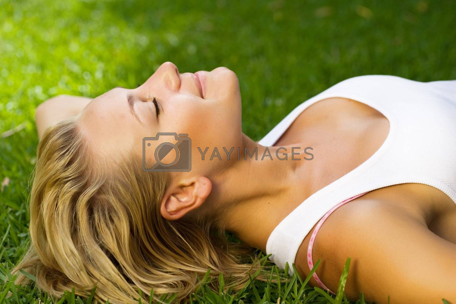 Beautiful Healthy Young Woman Lying On The Green Grass by SubbotinaA
