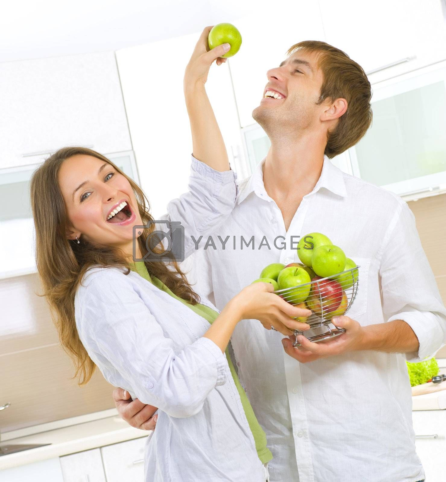 Happy Couple Eating fresh fruits.Having fun on a kitchen.Dieting by Subbotina Anna
