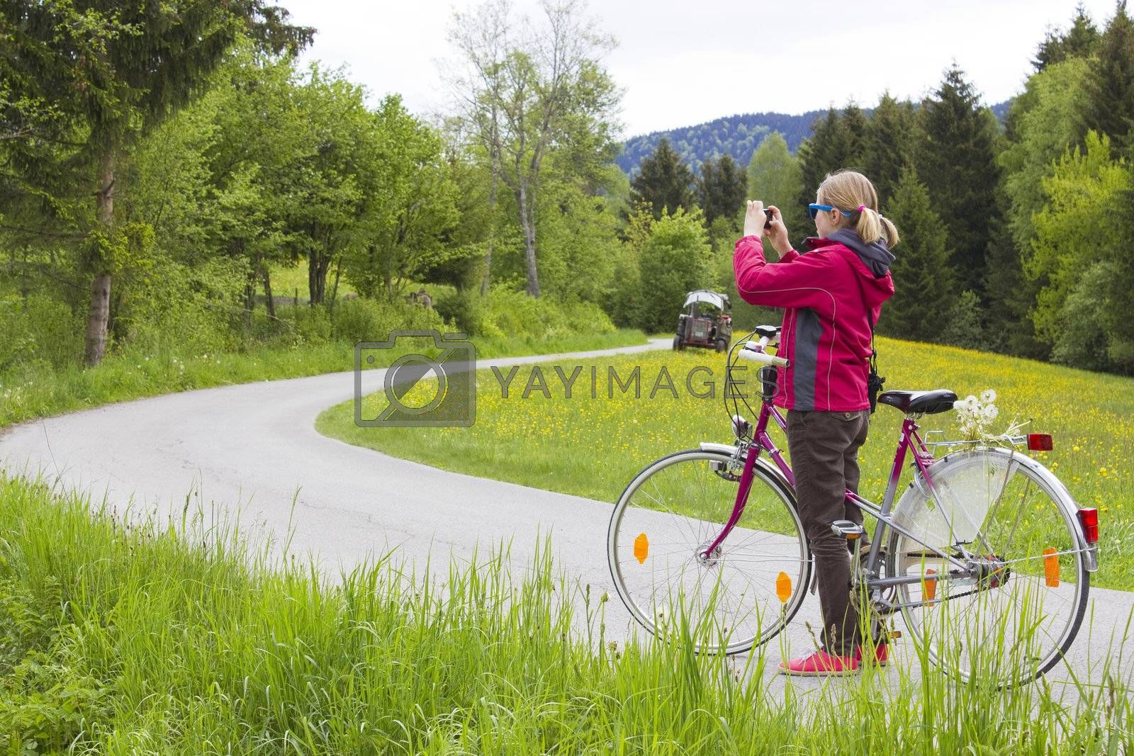 young girl with the bike in the mountains