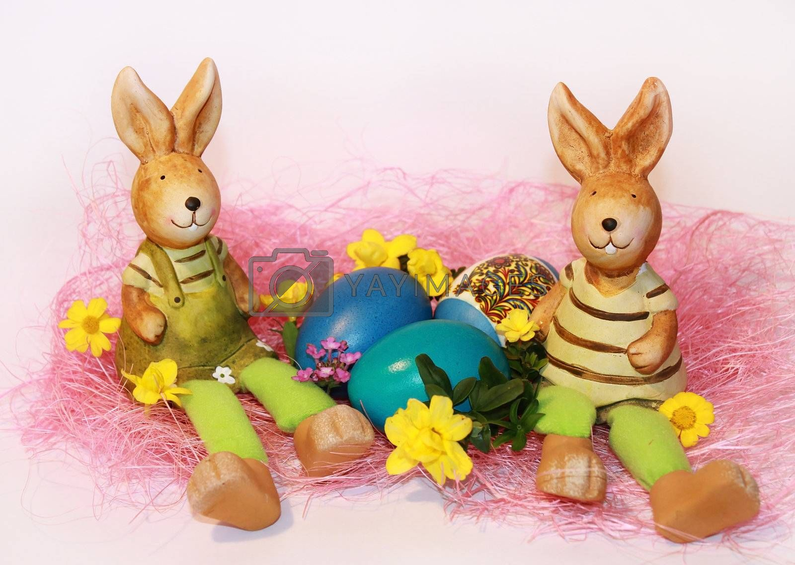toy rabbits are sitting near the dyed Easter eggs on a white background