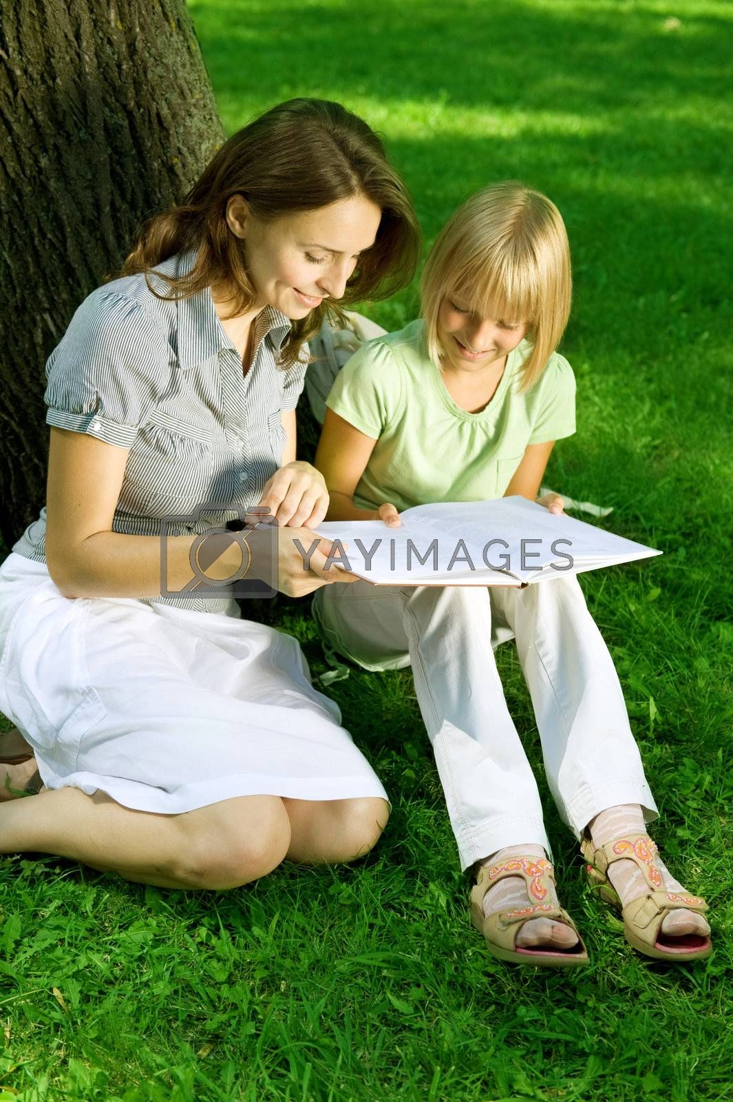 Mother And Daughter Reading The Book In A Park. Education Concep by Subbotina Anna