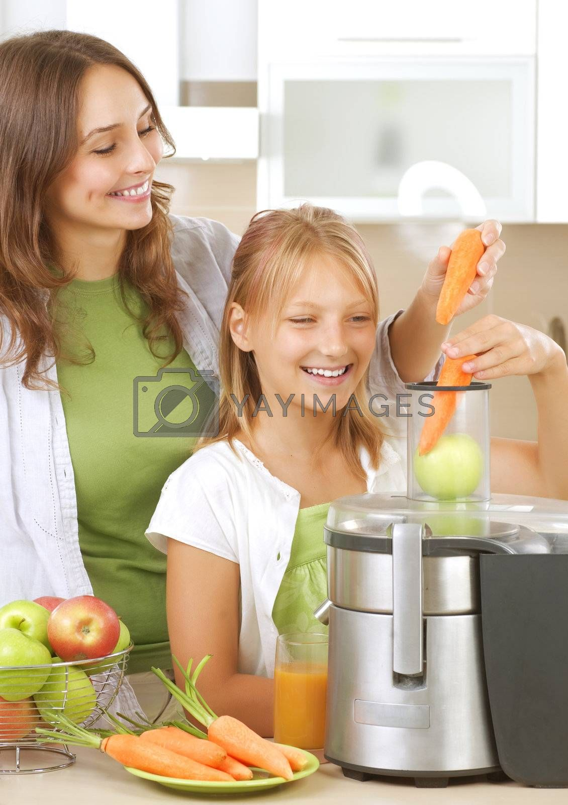 Happy Mother with Daughter eating Healthy food. Kitchen. Healthy by Subbotina Anna