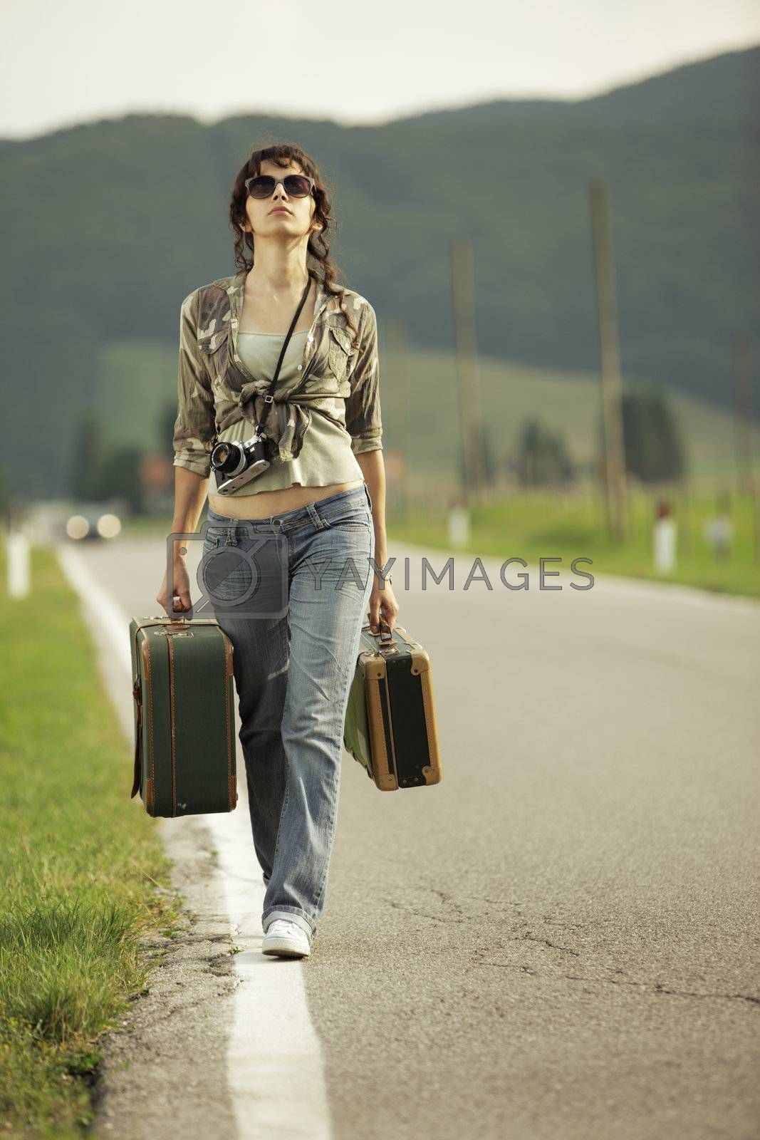 Young woman runaway walks away road
