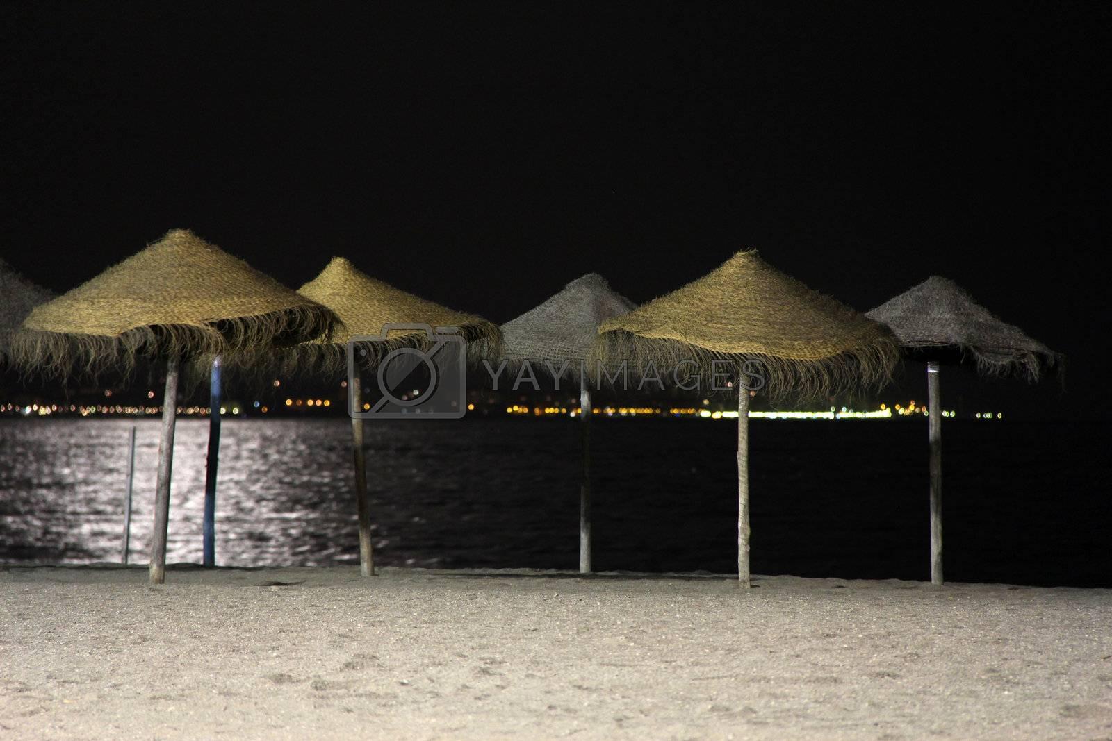 Straw umbrellas at night at the beach