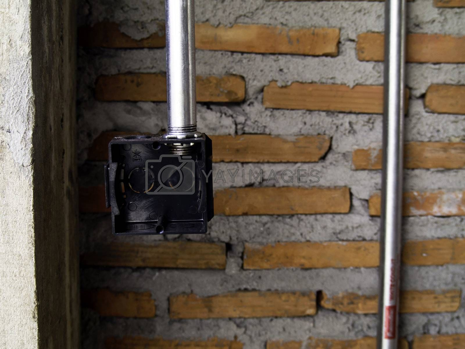Plastic box for electrical work with brick wall background