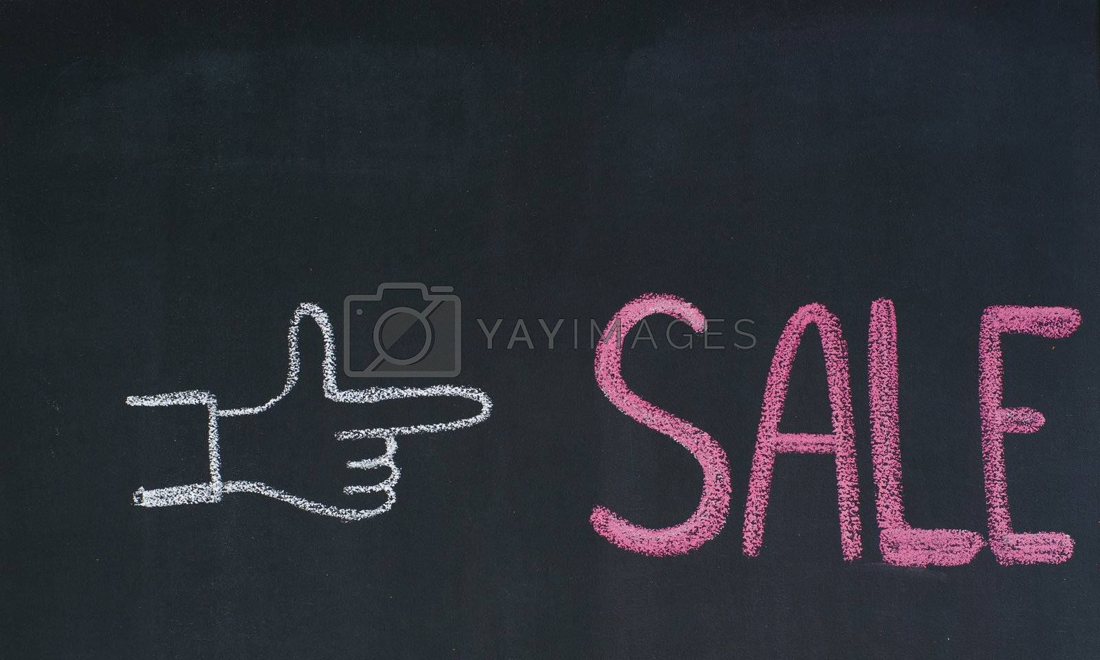 Hand pointing to the word Sale, written on a blackboard