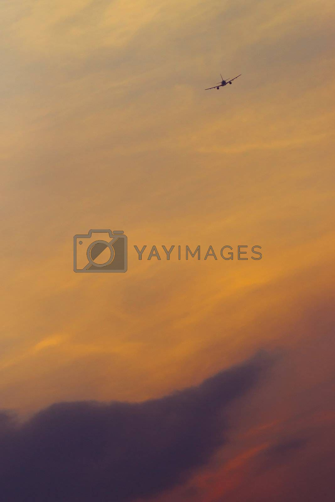 Airplane flying to the sunset sky