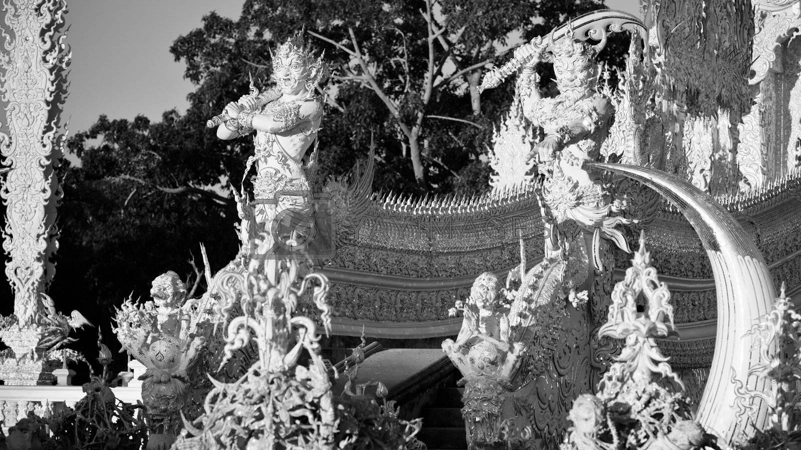 Statues of mythological guardians in white temple Wat Rong Khun.  Wat Rong Khun is a contemporary unconventional Buddhist temple in Chiang Rai, Chiangmai province, Thailand. It is designed in white color.