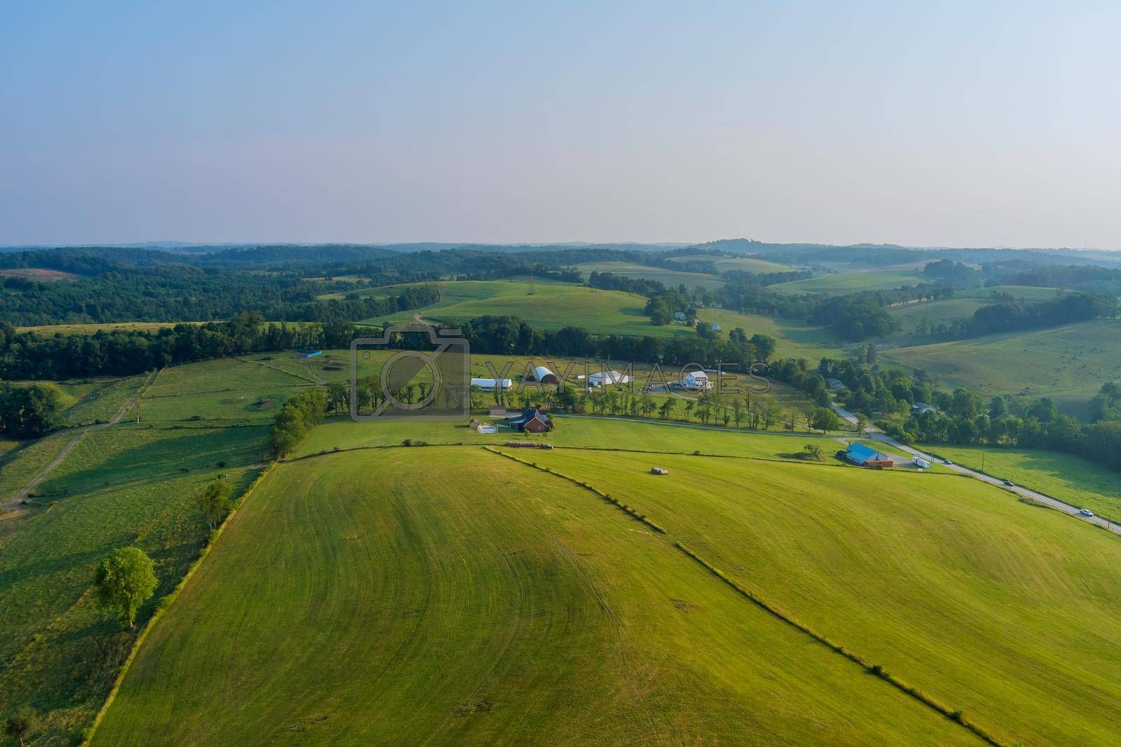 Royalty free image of A small Bentleyville town village behind trees and hills the farm meadow in Pennsylvania, US by ungvar