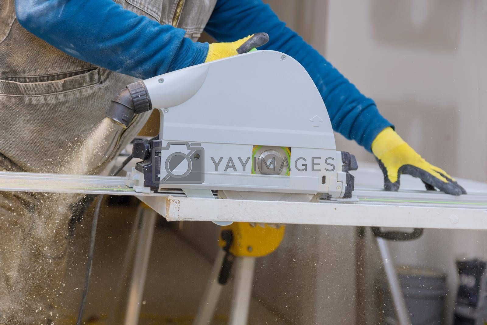 Royalty free image of Close Up process cutting of hand circular saw at wood door cuts by ungvar