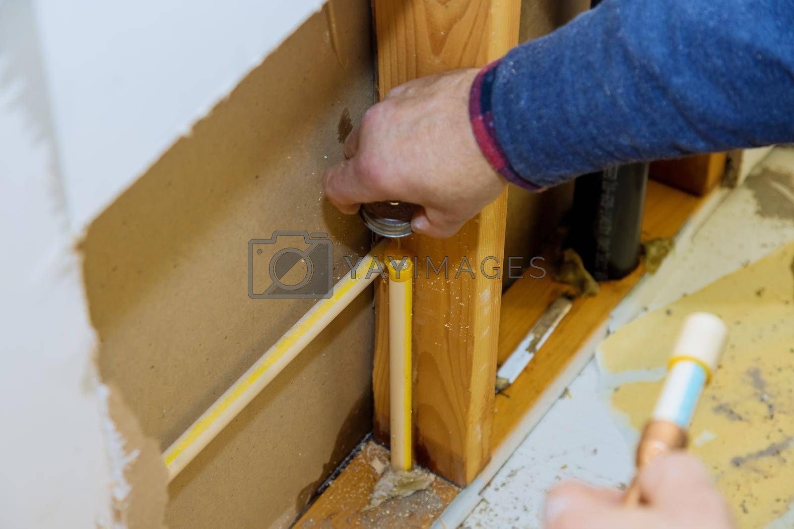 Royalty free image of Man manual cuts off a piece of polypropylene pipes for installation water line by ungvar