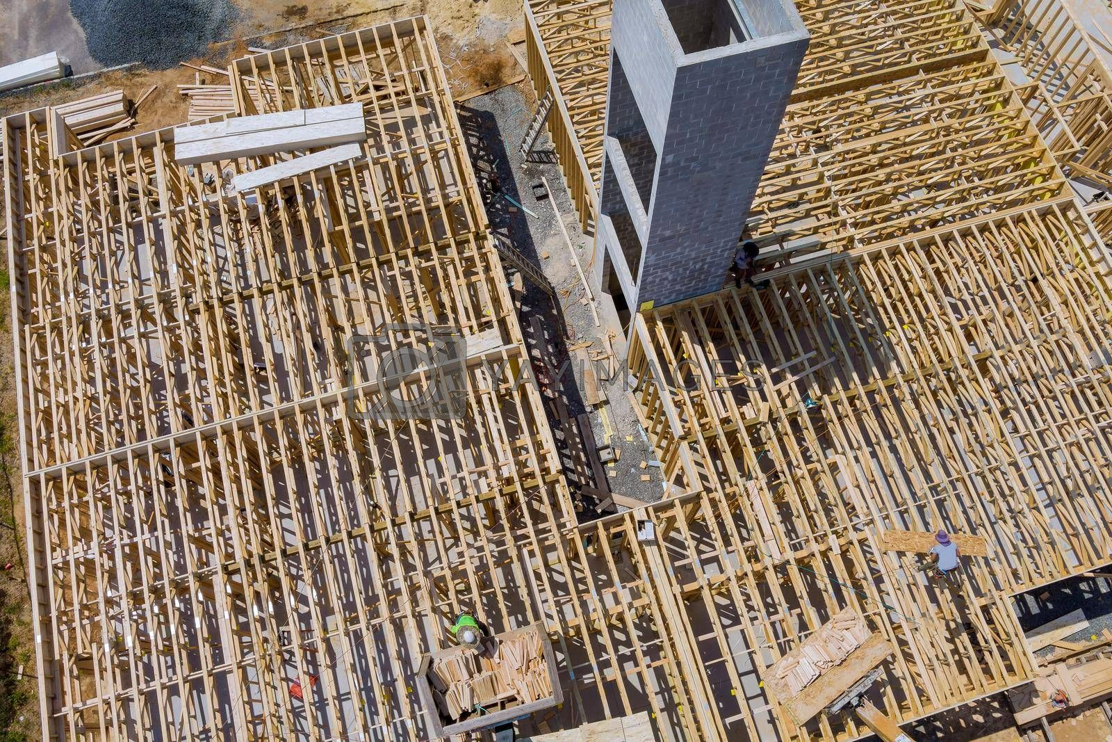 Royalty free image of A woodentruss being lifted by a boom truck forklift in the building materials a stack of boards wood frame a new home by ungvar