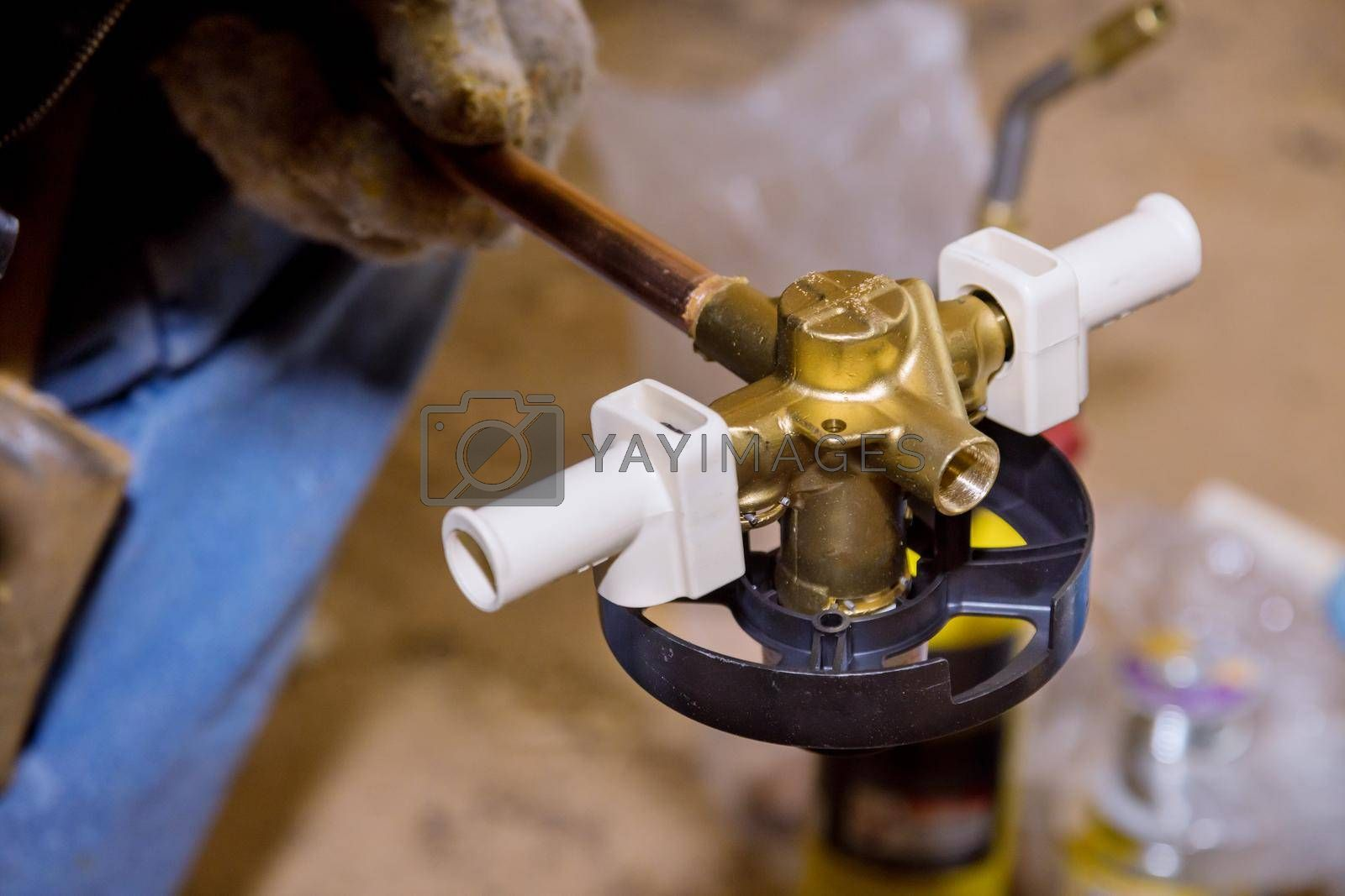 Royalty free image of Soldering brass fitting on copper pipe with torch of welding by ungvar