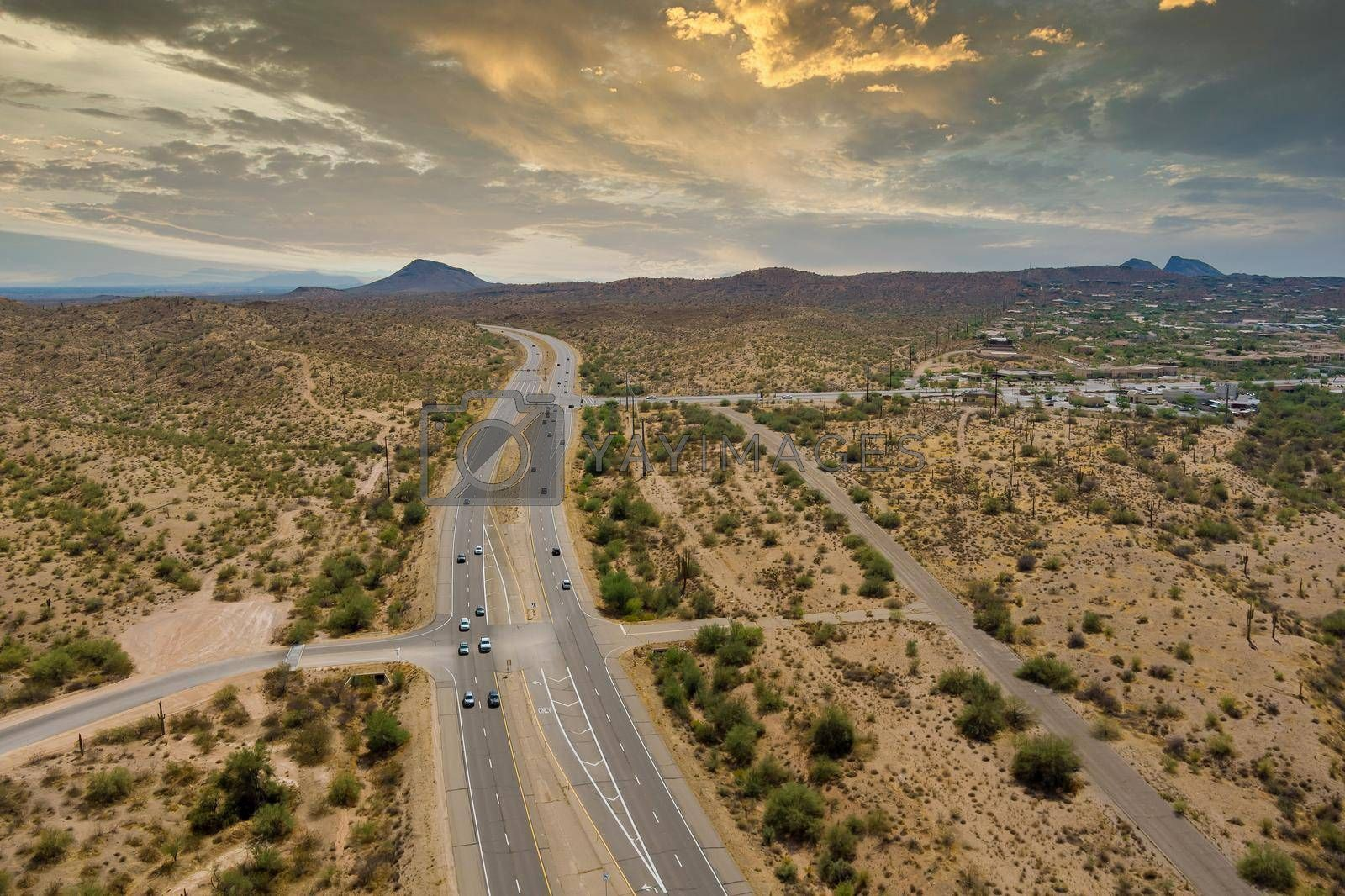 Royalty free image of Aerial view highway across the arid desert Arizona mountains adventure traveling desert road near Fountain Hills small town residential district by ungvar