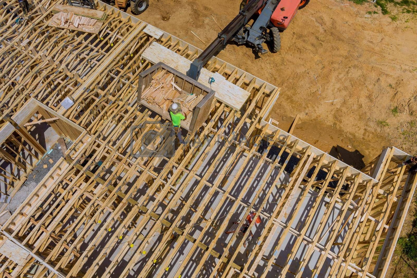 Royalty free image of Wood building frame on new residential construction home framing home boom truck forklift in the new home by ungvar