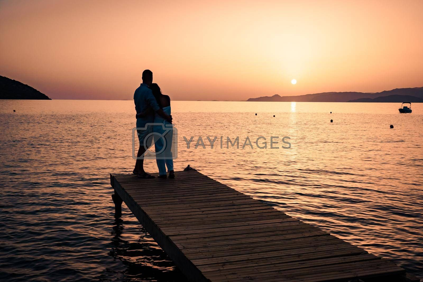 a couple seated on a wooden jetty, looking at colorful sunset on the sea, men, and women watching a sunset in Crete Greece Europe