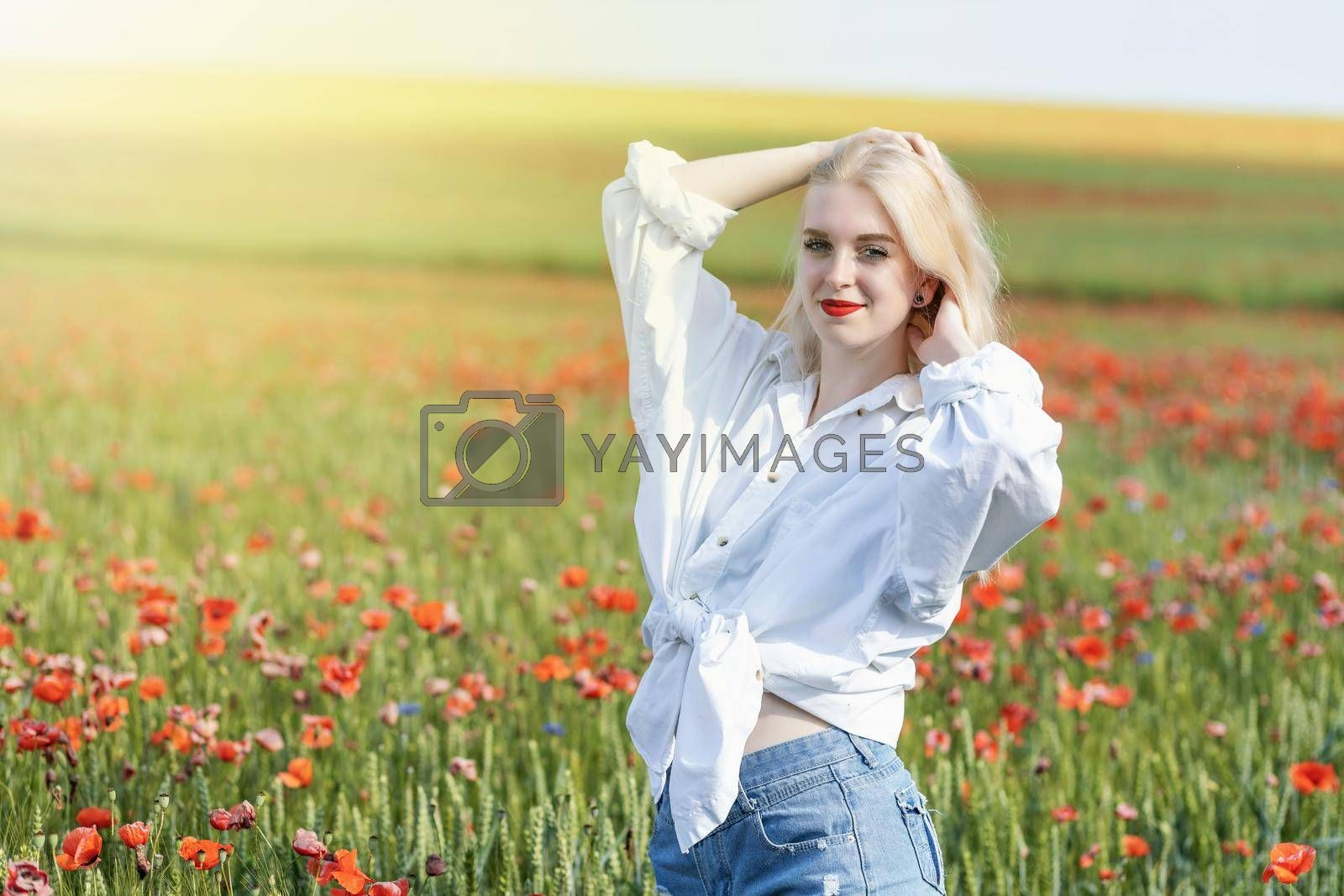 Royalty free image of Attractive young girl posing in a field with red poppies. by Frank11