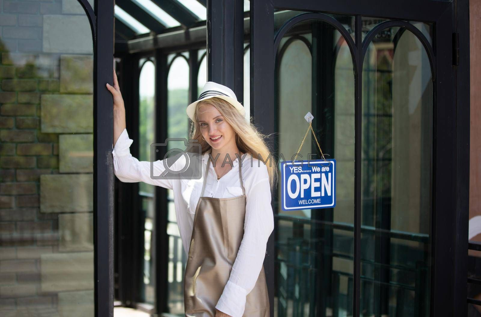 Royalty free image of Beautiful blonde hair girl standing with confidence in front of open coffee shop. by chuanchai