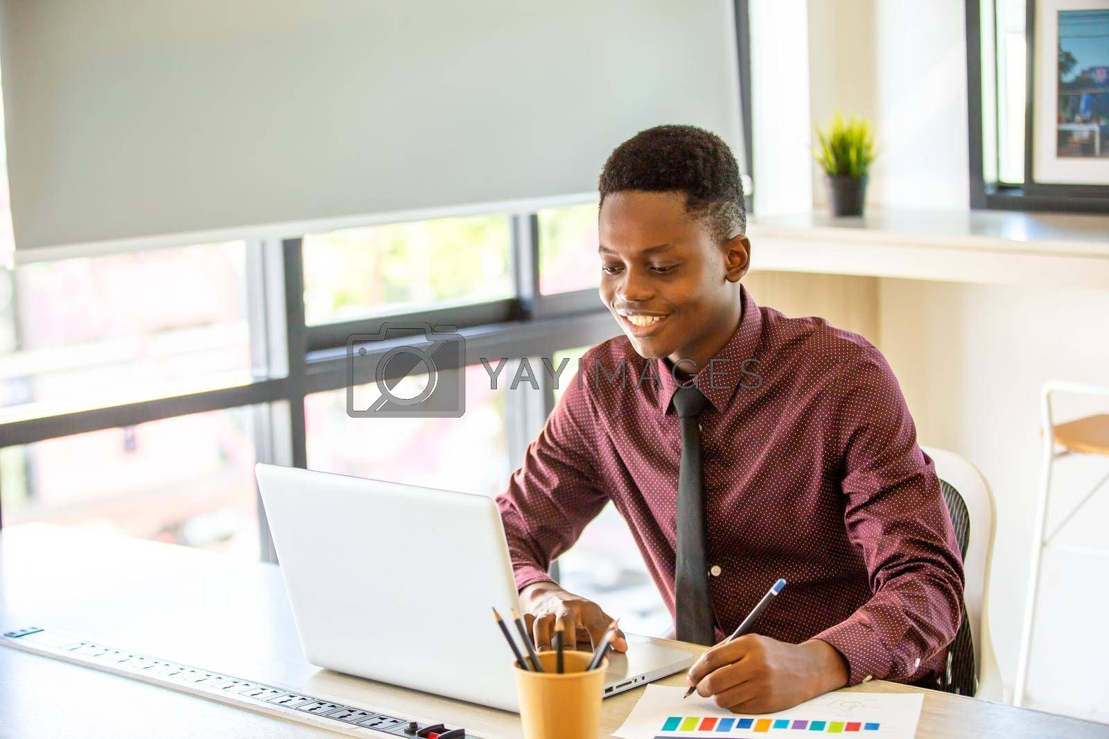 Royalty free image of Black man watching educational webinar on laptop, studying, preparing for exam, talk in video chat by chuanchai