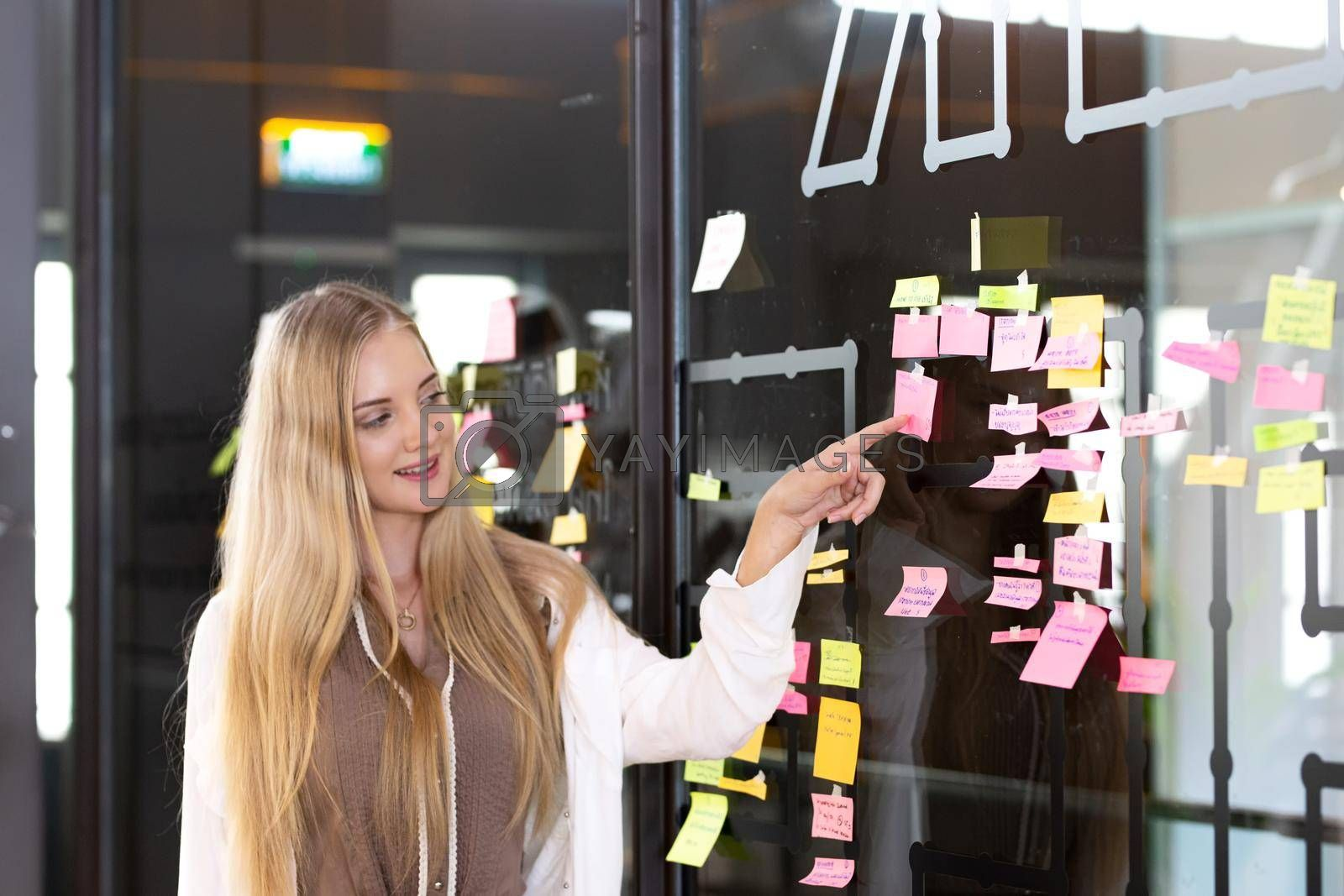 Royalty free image of Young women sticking post-its on an idea board. Brainstorming and organizing, whiteboard, chalkboard by chuanchai