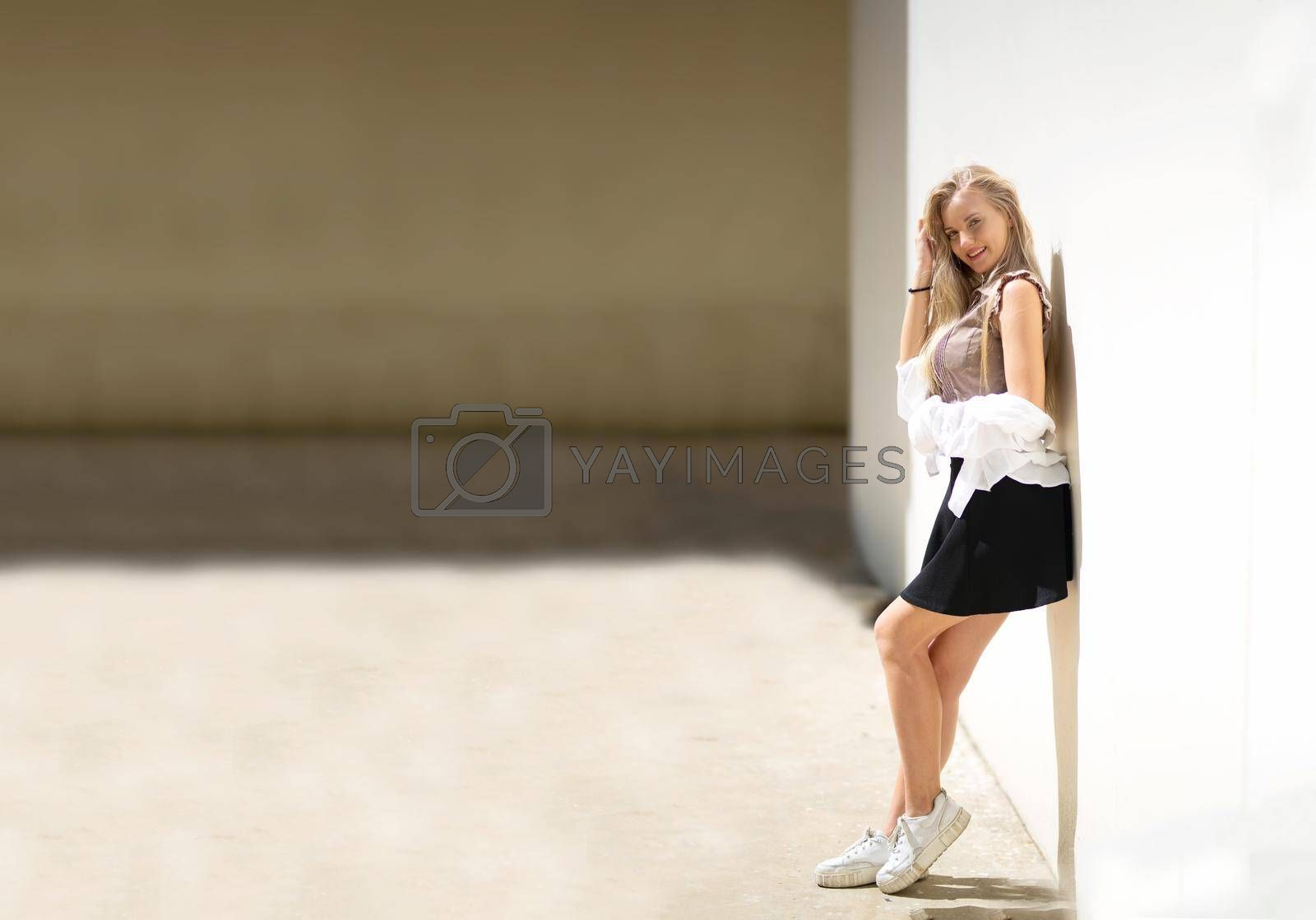 Royalty free image of Portrait of young beautiful woman blonde hair standing against wall with copy space by chuanchai