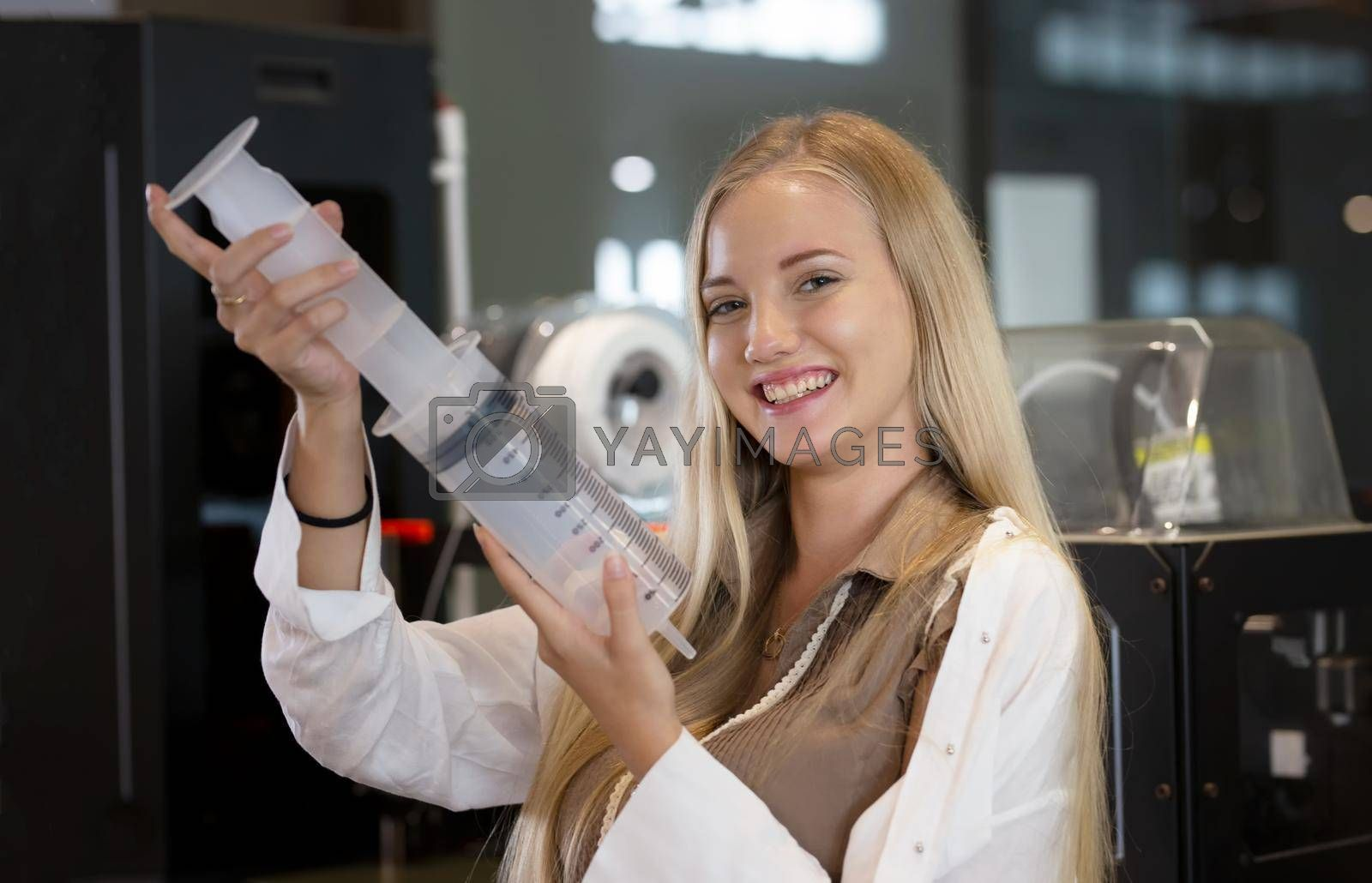 Royalty free image of Young smiling woman analyzing machine part during her scientific experiment in laboratory. by chuanchai