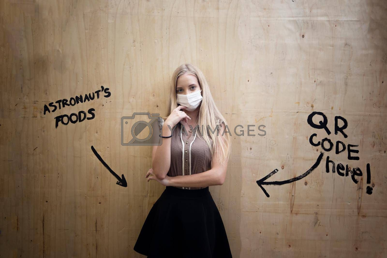 Royalty free image of Portrait of smiling woman with mask against wall. by chuanchai